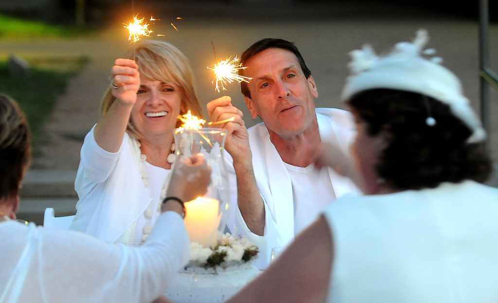 . Marilyn and Brent Marmo enjoy dinner with friends Lynn Johnson, far left, and Heidi Viestors, far right, during their first Dinner in White at the Minneapolis Sculpture Park on Saturday, July 20, 2013. About 350 people attended the third annual flash-mob-style dinner party. (Pioneer Press: Sherri LaRose-Chiglo)