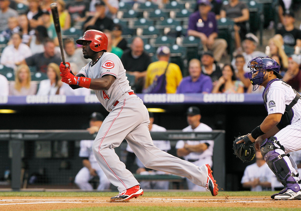 . Cincinnati Reds\' Brandon Phillips, left, follows the flight of his RBI-triple with Colorado Rockies catcher Wilin Rosario in the first inning of a baseball game in Denver on Saturday, Aug. 31, 2013. (AP Photo/David Zalubowski)