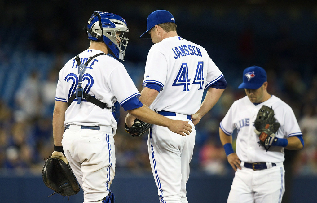 . Toronto Blue Jays catcher Josh Thole goes out to talk to pitcher Casey Janssen with Jays third baseman Steve Tolleson after Janssen gave up three runs and the lead to the Detroit Tigers in the ninth inning of a baseball game, Friday, Aug. 8, 2014 in Toronto. (AP Photo/The Canadian Press, Fred Thornhill)
