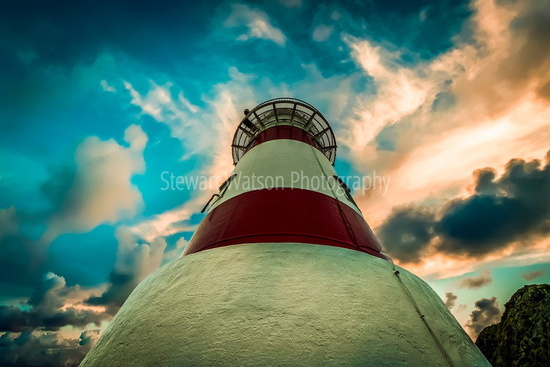 Looking up the lighthouse to stormy skies above