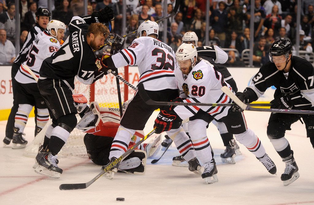 . The Kings\' Jeff Carter (#77) loses his helmet as the Blackhawks\' Brandon Saad and the Kings\' Tyler Toffoli go for the puck during game six of the Western Conference Finals, Friday, May 30, 2014, at Staples Center. (Photo by Michael Owen Baker/Los Angeles Daily News)