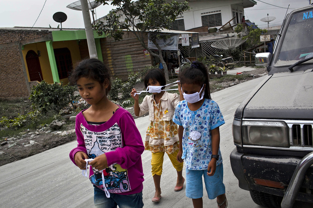 . Children wear masks while passing through an area covered by ash after Mount Sinabung erupted spewing volcanic materials in Karo district on November 14, 2013 in Medan, Sumatra, Indonesia. Up to 4,300 residents have been evacuated from five villages in North Sumatra due to the volcanic eruptions of Mount Sinabung. The volcano has been erupting for several days, spewing ash and lava 2.5 miles into the sky.  (Photo by Ulet Ifansasti/Getty Images)