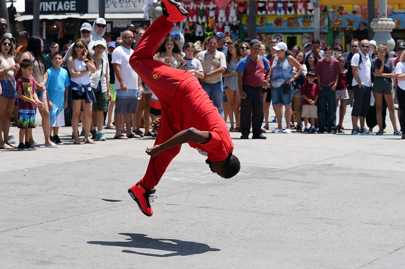 A street performer does a flip in Venice Beach