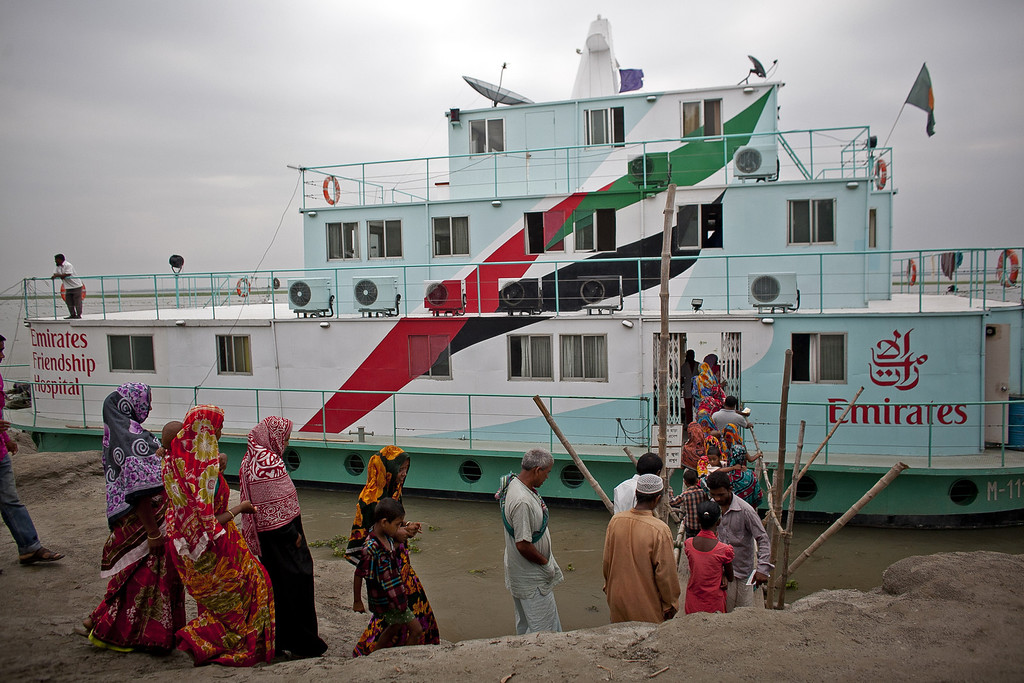 """. Patients enter the Emirates Friendship Floating Hospital May 19, 2014 in Chilmari district, Bangladesh. Friendship floating hospitals dock for up to 5 months at remote islands, or \""""chors\"""", in the north of Bangladesh with a full medical team and stocked pharmacy, providing health care at affordable cost.  (Photo by Allison Joyce/Getty Images)"""