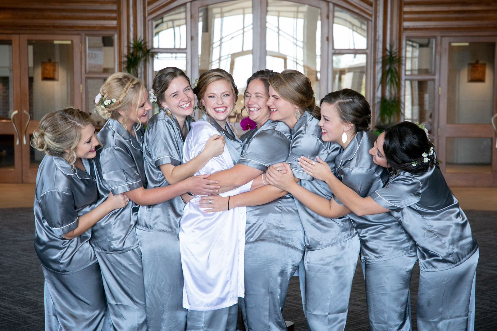 bridesmaids wearing matching silk pajamas all hugging a bride on her wedding day