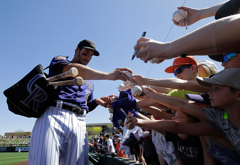 . Colorado Rockies third baseman Nolan Arenado signs autographs for fans before a spring training baseball game between the Rockies and the Milwaukee Brewers in Scottsdale, Ariz., Tuesday, March 22, 2016. (AP Photo/Jeff Chiu)