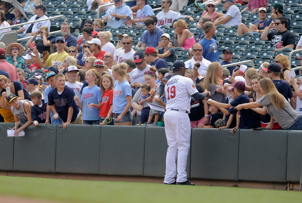 . Minnesota Twins\' Kennys Vargas sign autographs for Twins\' fans prior to the Twins game against the Detroit Tigers in a baseball game in Minneapolis, Sunday, Aug. 24, 2014. (AP Photo/Tom Olmscheid)