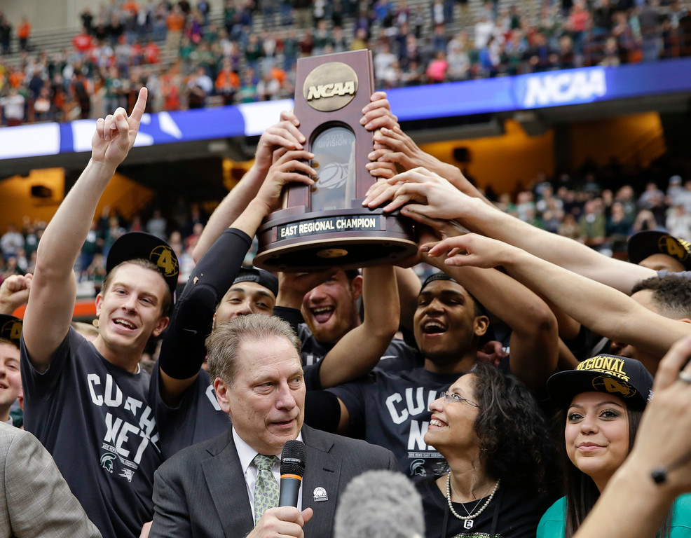 . Michigan State players hold the East Regional championship trophy as coach Tom Izzo speaks after the regional final against Louisville in the NCAA men\'s college basketball tournament Sunday, March 29, 2015, in Syracuse, N.Y. Michigan State won 76-70. (AP Photo/Seth Wenig)