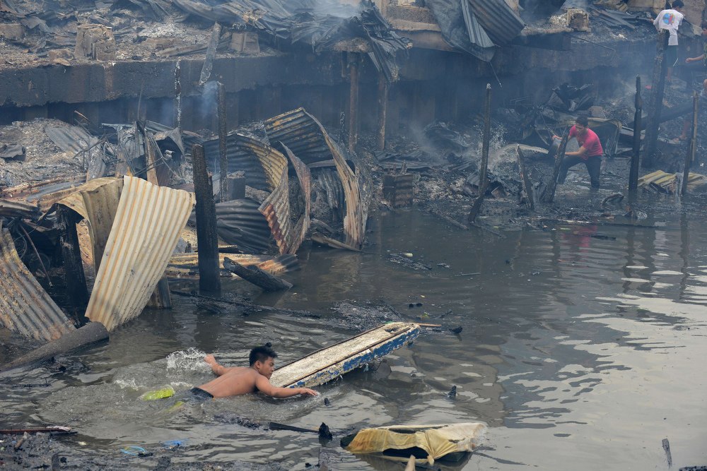 . Residents wade through water searching for salvageable materials after a fire razed a slum area in Manila on July 24, 2013. Almost 200 houses were destroyed, leaving 400 residents homeless, according to a local media report. NOEL CELIS/AFP/Getty Images