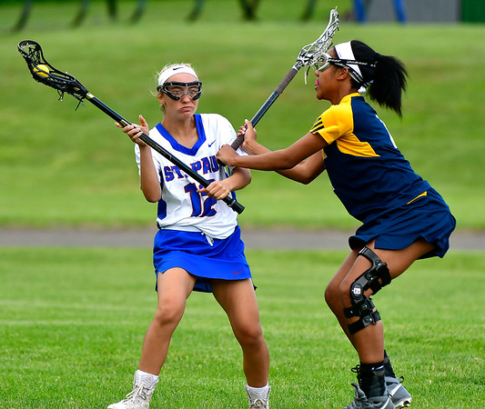 5/29/2019 Mike Orazzi | Staff St. Paul's Christina Pisani (12) and Weston's Jasmine Butcher (4) during Wednesday's Class S First Round lacrosse match in Bristol.