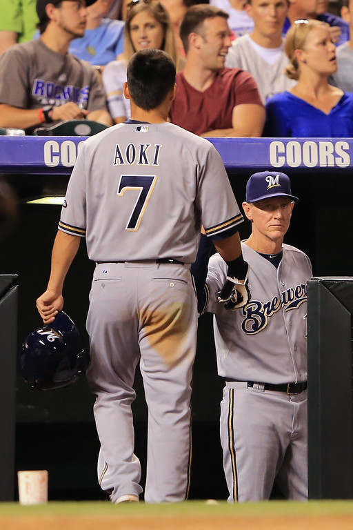. DENVER, CO - JULY 26:  Norichika Aoki #7 of the Milwaukee Brewers is welcomed back to the dugout after scoring against the Colorado Rockies by manager Ron Roenicke #10 of the Milwaukee Brewers in the sixth inning at Coors Field on July 26, 2013 in Denver, Colorado.  (Photo by Doug Pensinger/Getty Images)