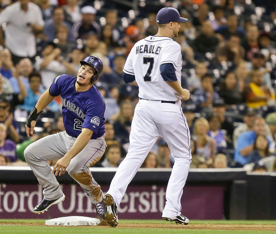 . Colorado Rockies\' Nolan Arenado bounces up from his slide after he stole third when San Diego Padres third baseman Chase Headley charged the bunt attempt of the Rockies\' batter and no one else covered the third base in the fourth inning of a baseball game in San Diego, Wednesday, July 10, 2013. (AP Photo/Lenny Ignelzi)
