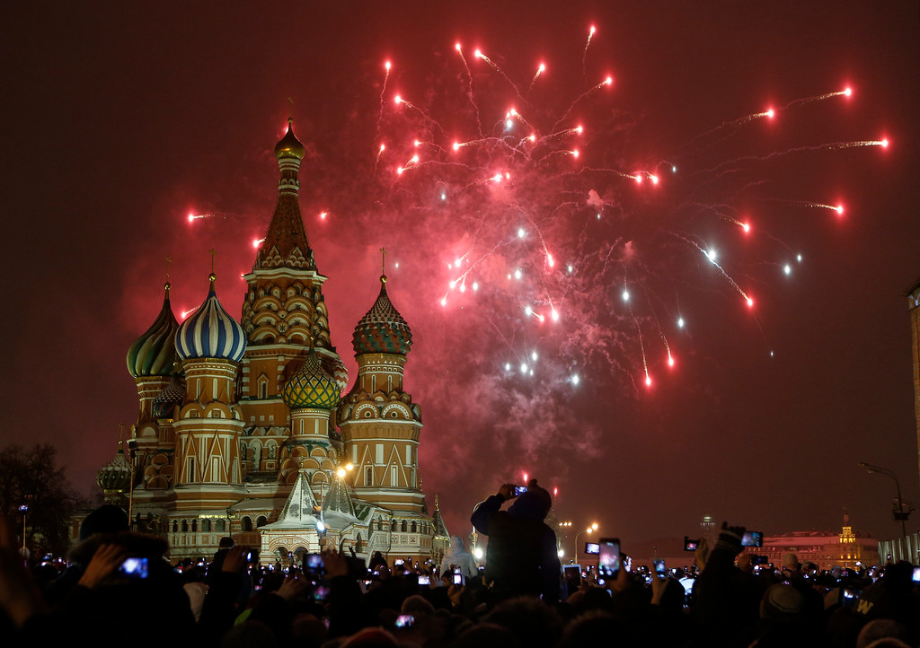 . People photograph fireworks as they celebrate the New Year in Red Square in Moscow, Russia, Thursday, Jan. 1, 2015. (AP Photo/Denis Tyrin)