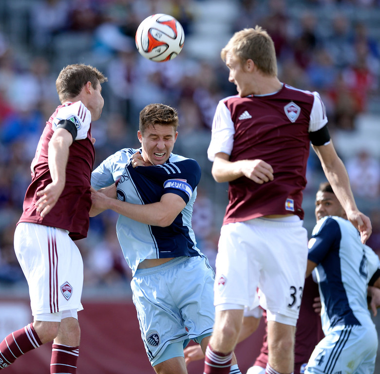 . Colorado defender Drew Moor, left, challenged Kansas City forward Matt Besler, center, on a corner kick in the first half. The Colorado Rapids hosted Sporting Kansas City Saturday evening, March 29, 2014 at Dick\'s Sporting Goods Stadium in Commerce City.  (Photo by Karl Gehring/The Denver Post)
