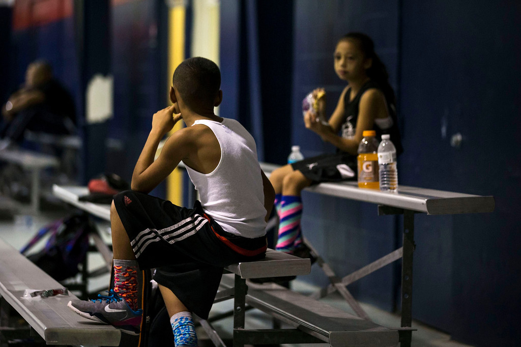 . Downey Christian high school varsity basketball player 11-year-old Julian Newman talks to a spectator (R) as he rests between Friday evening pickup basketball games at Downey Christian School in Orlando, Florida February 22, 2013. At 4 feet 5 inches tall, starting point guard Julian Newman stands waist high next to other players on his Florida high school basketball team. But his talent towers over the competition. At only 11, Newman leads the state of Florida in assists per game this season and ranks fifth nationally, according to Maxpreps.com, which maintains statistics on high school sports.  REUTERS/Scott Audette
