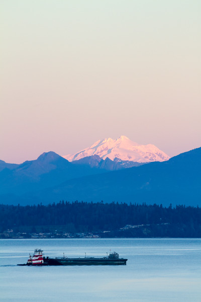 A tugboat pushes a barge I'm Puget sound, passed mountains at sunrise