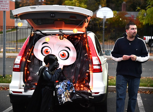 10/18/2019 Mike Orazzi | StaffrJoe Smith passes out candy during a trunk or treat held at the Greene-Hills School in Bristol on Friday evening.