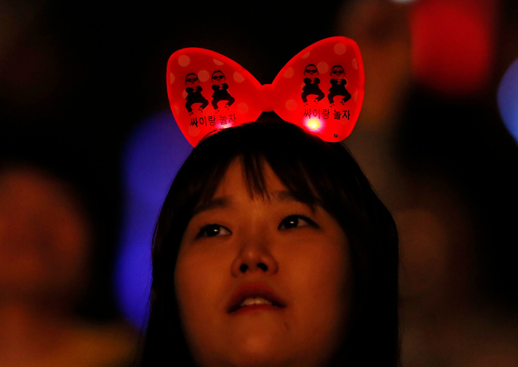 """. A fan of South Korean rapper PSY attends the concert \""""Happening\"""" in Seoul, South Korea Saturday, April 13, 2013. South Korean pop star PSY\'s first new single since his viral hit \""""Gangnam Style\"""" is stealing attention from inter-Korean tensions. (AP Photo/Kin Cheung)"""