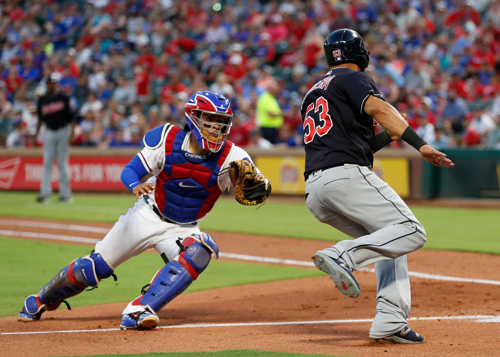 . Cleveland Indians\' Melky Cabrera (53) avoids a tag by Texas Rangers catcher Robinson Chirinos, left, to score on a single hit by teammate Yan Gomes during the fifth inning of a baseball game, Saturday, July 21, 2018, in Arlington, Texas. (AP Photo/Jim Cowsert)