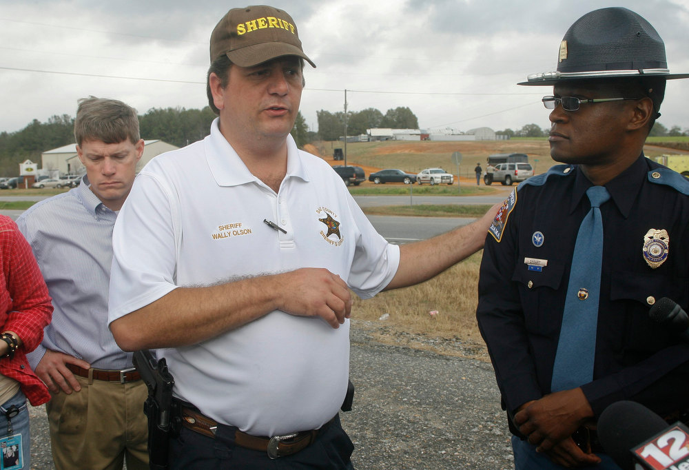 Description of . Dale County Sheriff Dale Olson and Alabama State Trooper Charles Dysert (R) speak to the media near the scene of a shooting and a standoff in Midland City, Alabama January 30, 2013. A standoff continued on Wednesday with a gunman who boarded an Alabama school bus and fatally shot the driver before fleeing with a young child and holing up in an underground bunker, authorities said.  REUTERS/Phil Sears