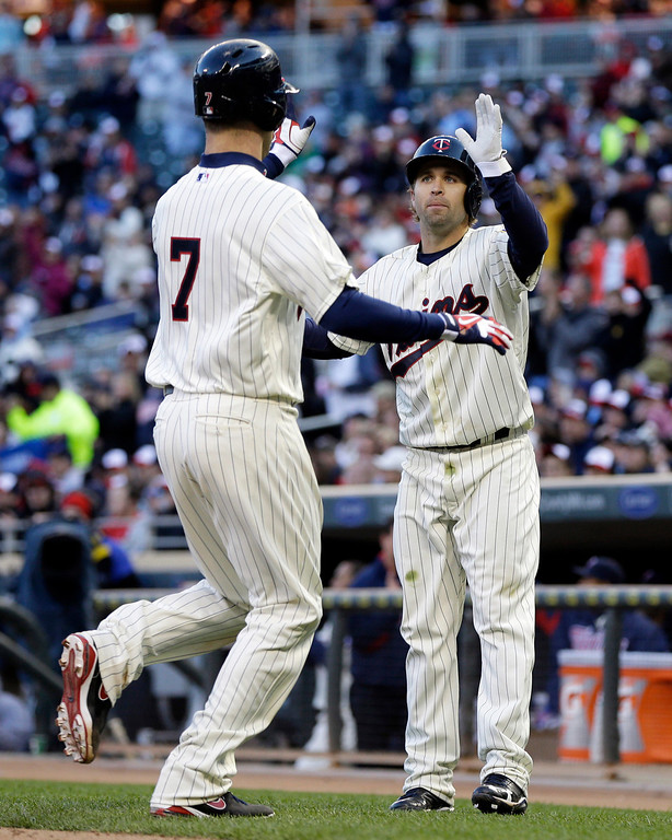 . Minnesota Twins\' Joe Mauer, left, and Brian Dozier celebrate as the two scored on a two-run single by Justin Morneau off Baltimore Orioles pitcher Steve Johnson in the fourth inning of a baseball game, Saturday, May 11, 2013 in Minneapolis. (AP Photo/Jim Mone)