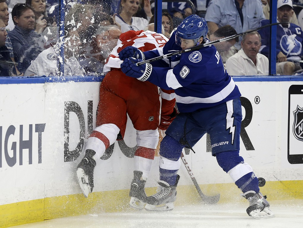. Tampa Bay Lightning center Tyler Johnson (9) checks Detroit Red Wings right wing Luke Glendening into the boards during the first period of Game 7 of a first-round NHL Stanley Cup hockey playoff series Wednesday, April 29, 2015, in Tampa, Fla. (AP Photo/Chris O\'Meara)