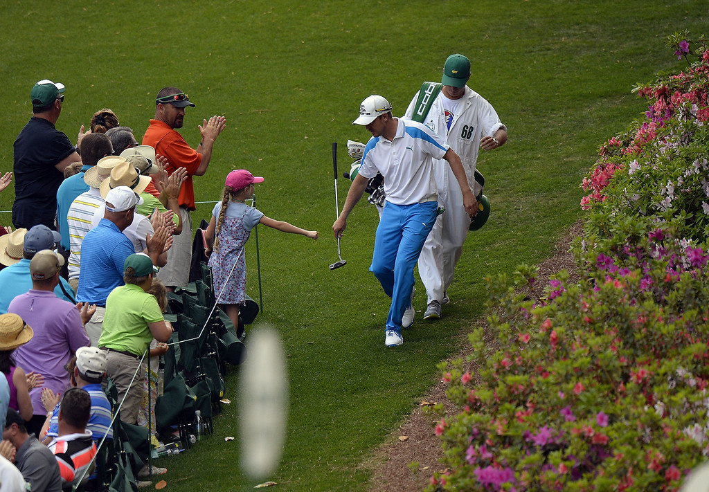 . Jonas Blixt of Sweden fist bumps with a young girl as he makes his way to play a shot during the final round of the 78th Masters Golf Tournament at Augusta National Golf Club on April 13, 2014 in Augusta, Georgia.   TIMOTHY A. CLARY/AFP/Getty Images