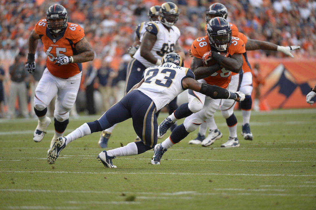 . DENVER, CO. - AUGUST 17: Denver Broncos running back Montee Ball (38) picks up some yards as St. Louis Rams safety Rodney McLeod (23) comes in for the tackle during the first quarter August 24, 2013 at Sports Authority Field at Mile High. (Photo By John Leyba/The Denver Post)
