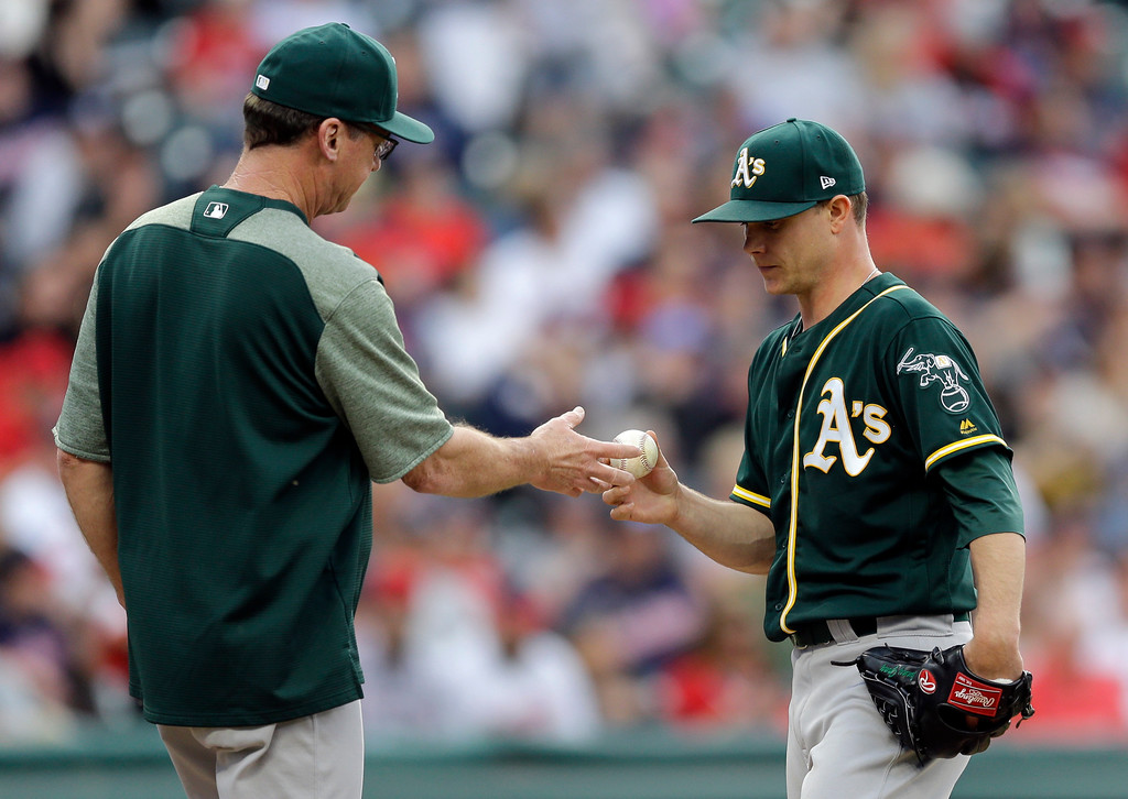 . Oakland Athletics starting pitcher Sonny Gray, right, gives the ball to Oakland Athletics manager Bob Melvin as Gray leaves the game in the fifth inning of a baseball game against the Cleveland Indians, Tuesday, May 30, 2017, in Cleveland. (AP Photo/Tony Dejak)