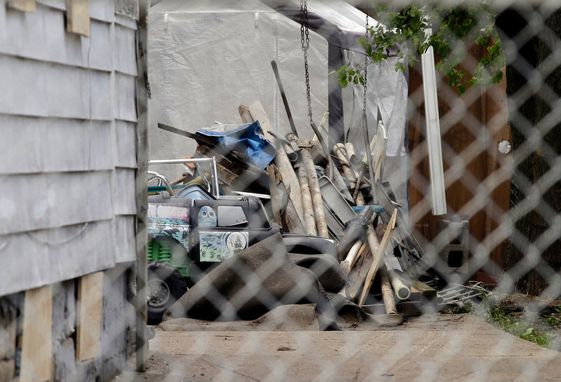 . Trash in the back yard of Ariel Castro\'s house in Cleveland is seen through a chain link fence Tuesday, May 14, 2013. Castro is under arrest and charged with kidnapping and rape after three women were rescued last week at the house after being held captive for a decade.   (AP Photo/Mark Duncan)