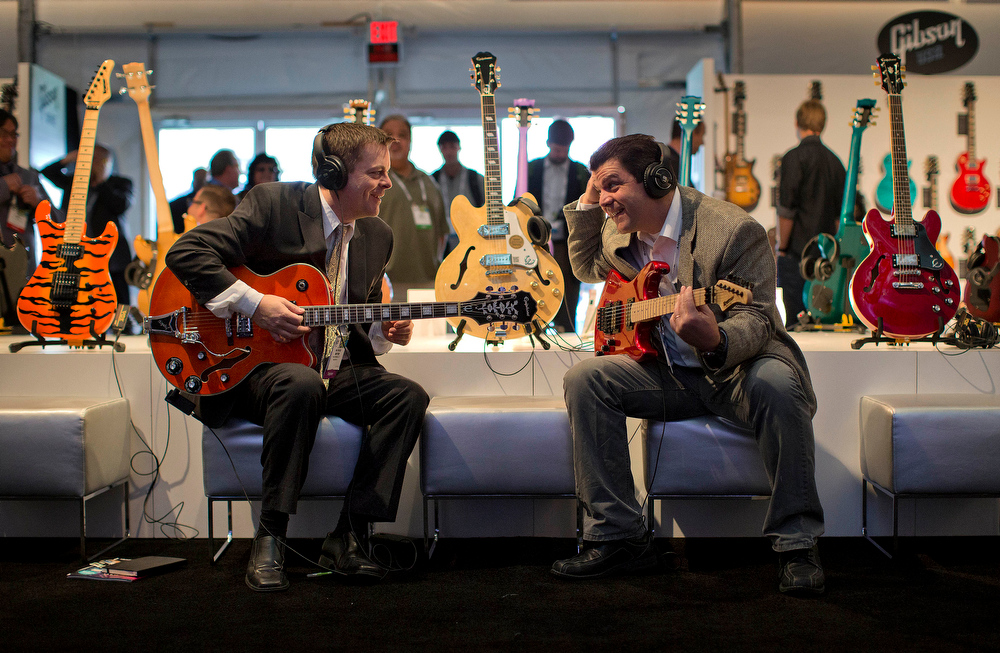 . Pace Wireless engineers Patrick Meyer, left, and Jamie McBain try out a variety of Gibson electric guitars on display at the International Consumer Electronics Show, Thursday, Jan. 9, 2014, in Las Vegas. (AP Photo/Julie Jacobson)