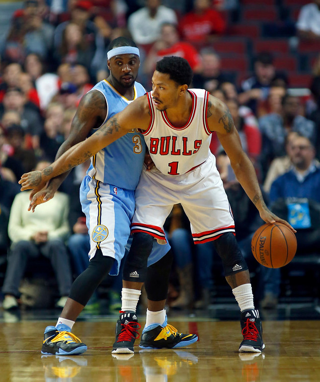 . Chicago Bulls guard Derrick Rose (1) is guarded by Denver Nuggets guard Ty Lawson (3) during the first half of a pre-season NBA basketball game in Chicago, on Monday Oct. 13, 2014. (AP Photo/Jeff Haynes)
