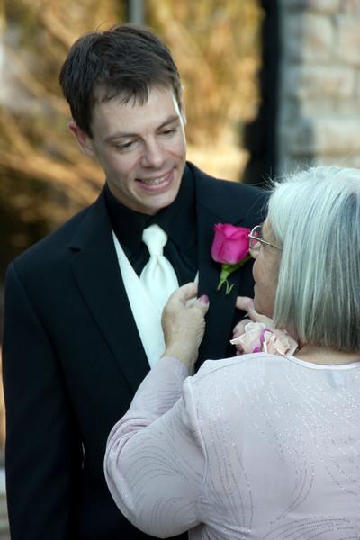 Groom's mom adjusts flower.