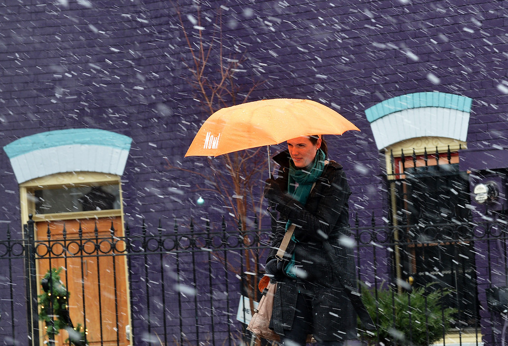 . A woman uses an umbrella as she cross a street during a snow storm in Washington, DC, on March 6, 2013. A massive winter storm pounding the northern US on March 6, grounded 2,600 flights, closed hundreds of schools and made roadways and highways impassible. At least four people were reportedly killed in accidents on icy and snow covered roads and highways. AFP PHOTO/Jewel SAMAD/AFP/Getty Images