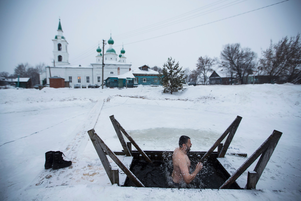 . A Russian Orthodox believer bathes in icy water on the Epiphany in the village of Sulost\', near Rostov, northeast from Moscow, Russia, Tuesday, Jan. 19, 2016. Water that is blessed by a cleric on Epiphany is considered holy and pure until next year\'s celebration, and is believed to have special powers of protection and healing. (AP Photo/Pavel Golovkin)