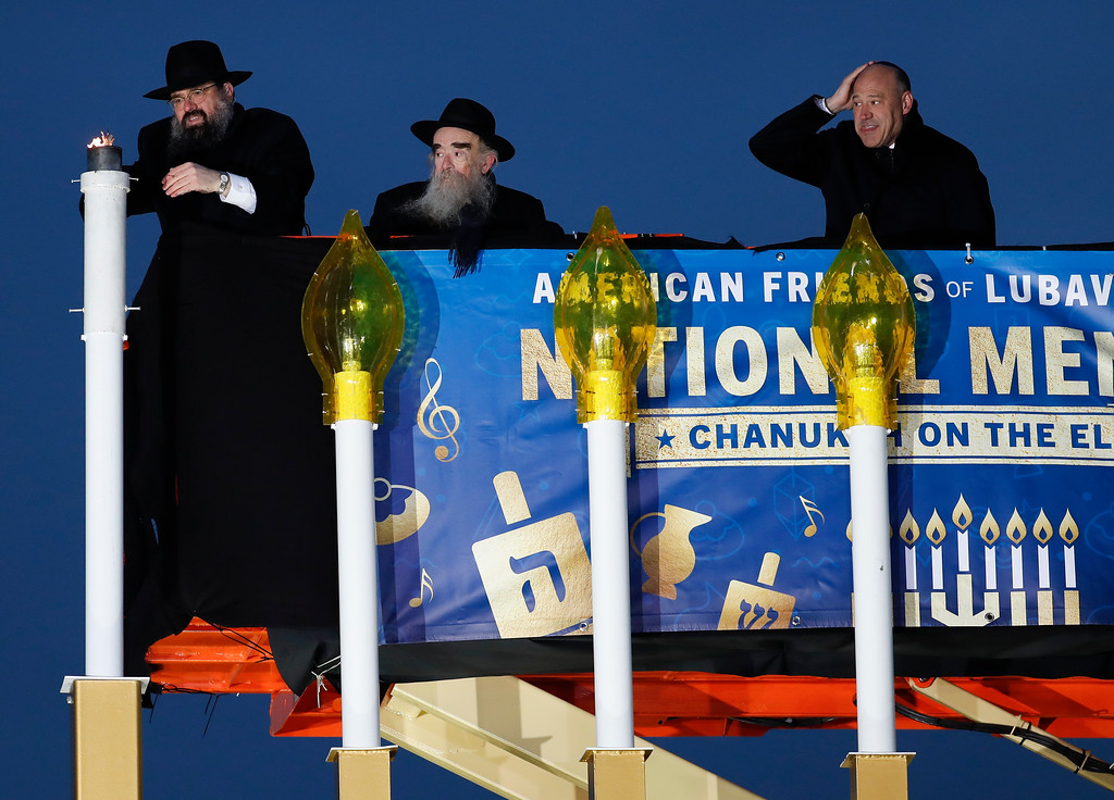 . From left, Rabbi Levi Shemtov, with Rabbi Abraham Shemtov and National Economic Director Gary Cohn, lights the Menorah during the annual National Menorah Lighting, in celebration of Hanukkah, on the Ellipse near the White House in Washington, Tuesday, Dec. 12, 2017. (AP Photo/Carolyn Kaster)