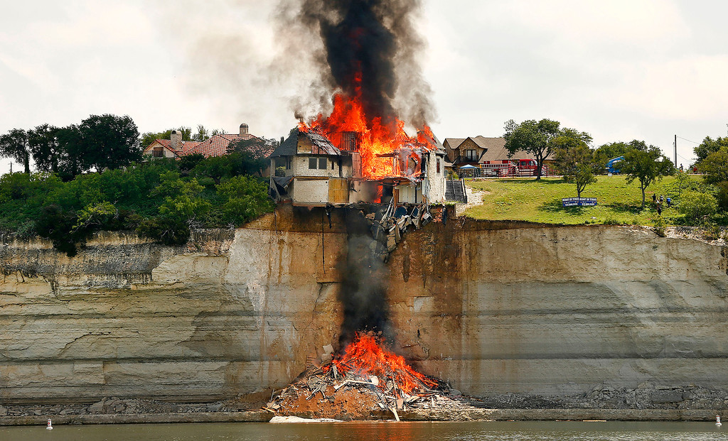 . A gated community White Bluff home is burned to save Lake Whitney from falling debris Friday June 13, 2014 in Lake Whitney, Texas. The White Bluff home is built on a fault line and is gradually collapsing with the cliff side into the lake. (AP Photo/The Fort Worth Star-Telegram, Ron Jenkins)