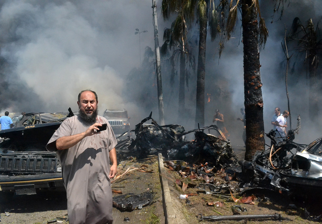 . A Lebanese man takes pictures with his mobile phone at the site of an explosion outside a mosque in the Northern city of Tripoli, Lebanon, Friday Aug. 23, 2013.  (AP Photo)