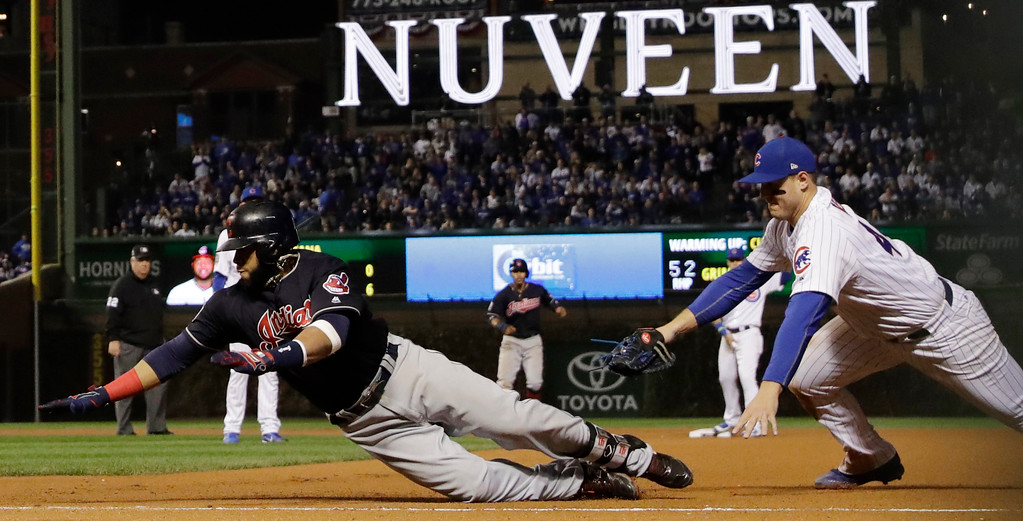 . Cleveland Indians\' Carlos Santana slides safely back to first as Chicago Cubs first baseman Anthony Rizzo tries to put a tag on him after a hit during the sixth inning of Game 4 of the Major League Baseball World Series Saturday, Oct. 29, 2016, in Chicago. (AP Photo/David J. Phillip)