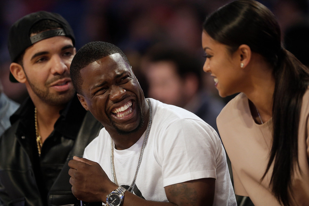 . Actor Kevin Hart, center laughs as Rapper Drake, left, looks on during the NBA All Star basketball game, Sunday, Feb. 16, 2014, in New Orleans. (AP Photo/Gerald Herbert)