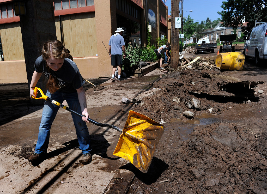 . MANITOU SPRINGS, CO - Aug.10: Amanda Bridger, left, joins with residents and crews as they clean up the damage and debris along Canon Avenue after a flash flood roared through the streets and hillsides on Friday evening. (Photo By Kathryn Scott Osler/The Denver Post)