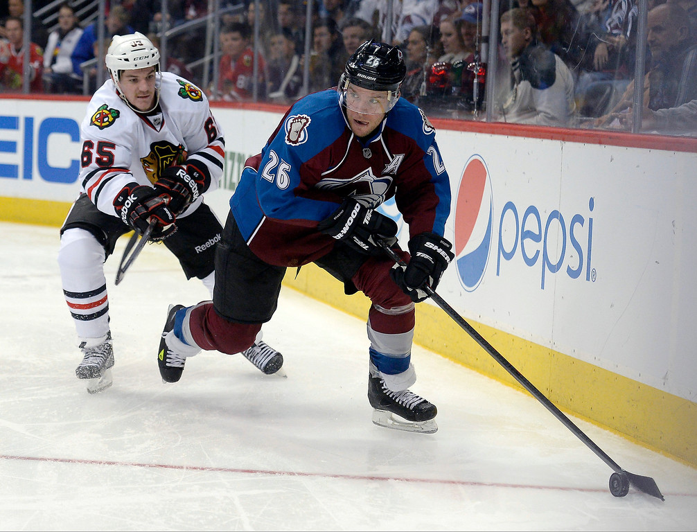 . Colorado Avalanche center Paul Stastny (26) skates the puck around the net as he gets chard by Chicago Blackhawks center Andrew Shaw (65) during the third period November 19, 2013 at Pepsi Center. (Photo by John Leyba/The Denver Post)