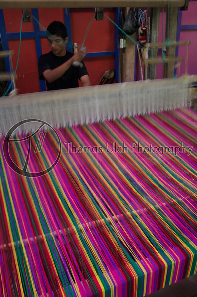 A fellow hard at work at the loom weaving a blanket.