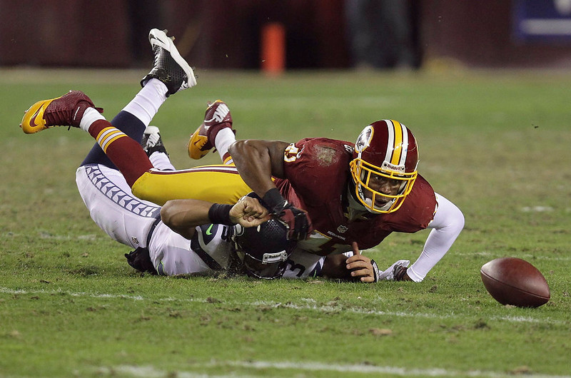 . Seattle Seahawks quarterback Russell Wilson (3) has the ball knocked loose as he is hit by Washington Redskins free safety Madieu Williams (41) during their NFL NFC wildcard playoff game in Landover, Maryland, January 6, 2013. REUTERS/Laurence Kesterson