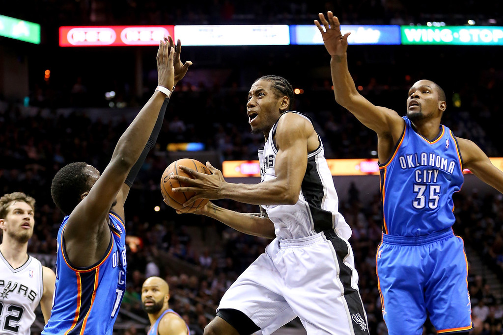 . Kawhi Leonard #2 of the San Antonio Spurs goes up for a shot between Reggie Jackson #15 and Kevin Durant #35 of the Oklahoma City Thunder in the first half in Game One of the Western Conference Finals during the 2014 NBA Playoffs at AT&T Center on May 19, 2014 in San Antonio, Texas.  (Photo by Ronald Martinez/Getty Images)