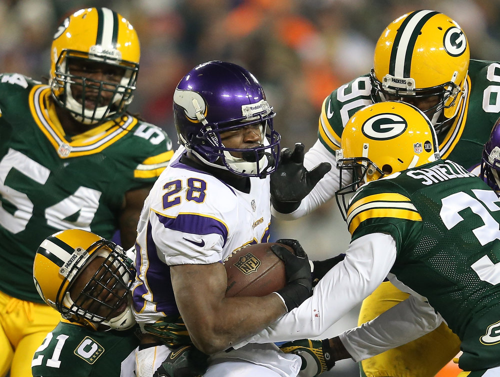 Description of . Running back Adrian Peterson #28 of the Minnesota Vikings runs the ball as he is tackled by strong safety Charles Woodson #21 and cornerback Sam Shields #37 of the Green Bay Packers in the first quarter during the NFC Wild Card Playoff game at Lambeau Field on January 5, 2013 in Green Bay, Wisconsin.  (Photo by Andy Lyons/Getty Images)