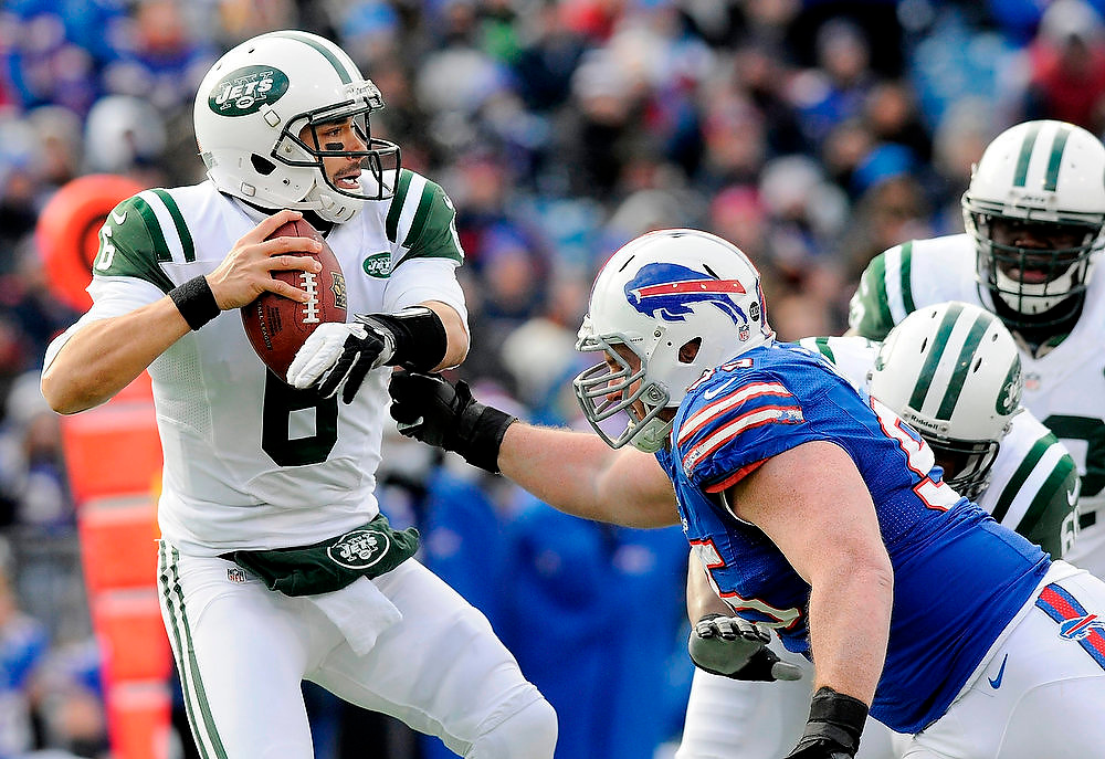 Description of . New York Jets quarterback Mark Sanchez (6) evades Buffalo Bills defensive tackle Kyle Williams (C) in the first quarter of their NFL football game in Orchard Park, New York December 30, 2012.       REUTERS/Doug Benz