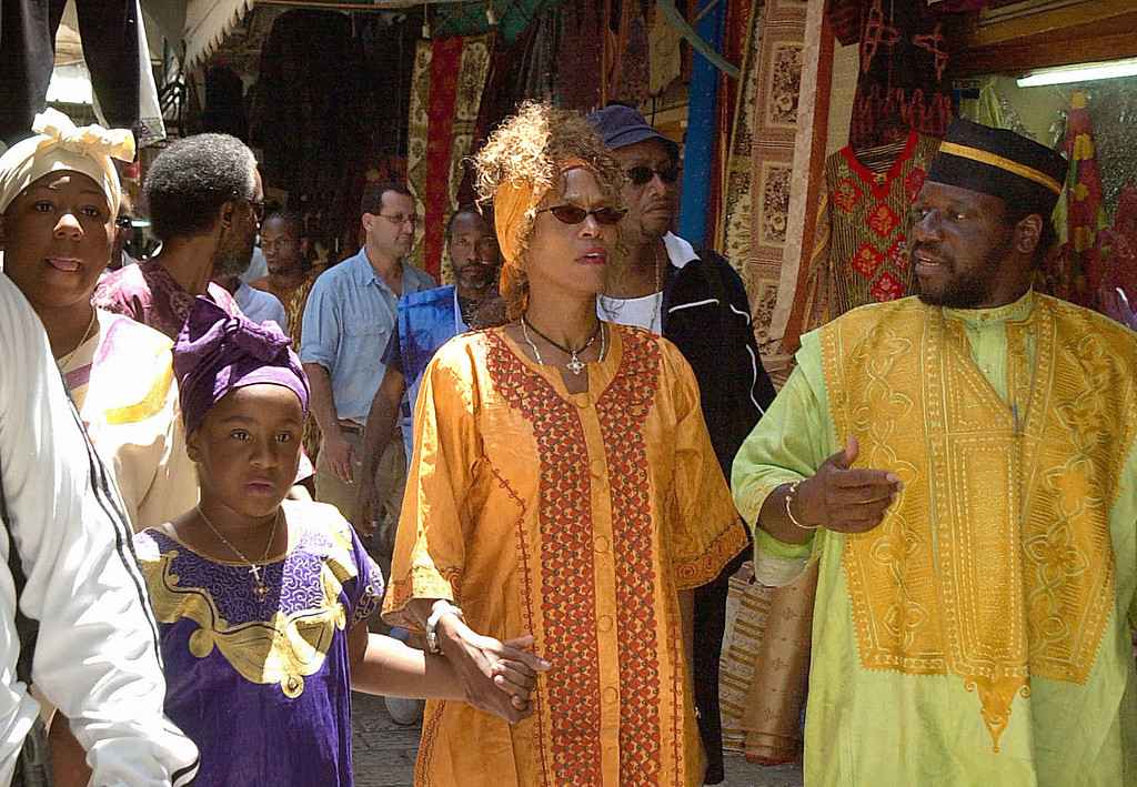 . US soul star Whitney Houston (C) and her daughter walk hand in hand through an alley in the old city of Jerusalem 28 May 2003.  (AFP/Getty Images)