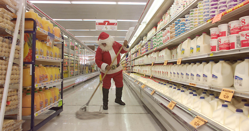 Description of . Maintenance worker Dagoberto Morale dressed as Santa Claus mops the milk and produce aisle at a food store Thursday. Dec. 13, 2001 in El Paso, Texas. He said he donned the Santa suit with the hopes of spreading cheer to store visitors. (AP Photo/El Paso Times, Victor Calzada)