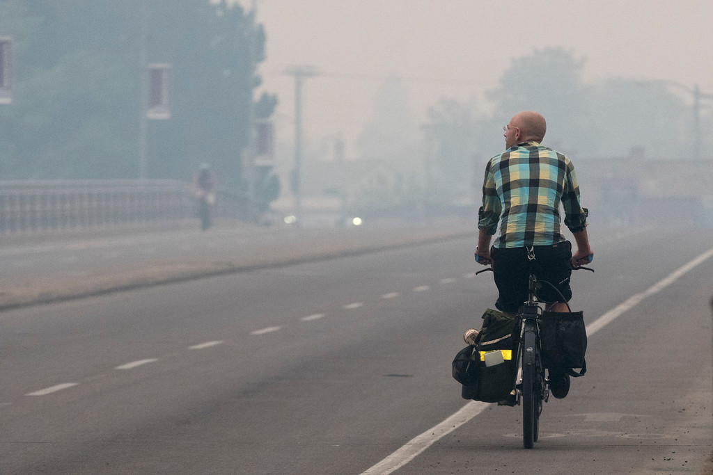 . A bicyclist makes his way down Higgins Avenue in Missoula, Mont. as smoke from the nearby Lolo Peak Fire fills the air on Monday, Sept. 4, 2017. The air quality is has been measured at hazardous by the Montana Department of Environmental Quality. (AP Photo/Patrick Record)